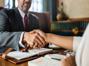 Two people shaking hands during a business meeting.